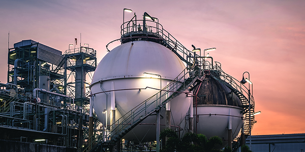 Gas storage sphere tanks in factories on sunset sky background