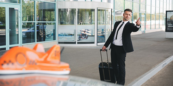 Serious businessman walking outside the airport with a suitcase and catching taxi